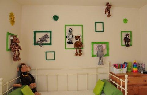 Kislányszoba festett antik képkeretekkel és plüsstrófeákkal